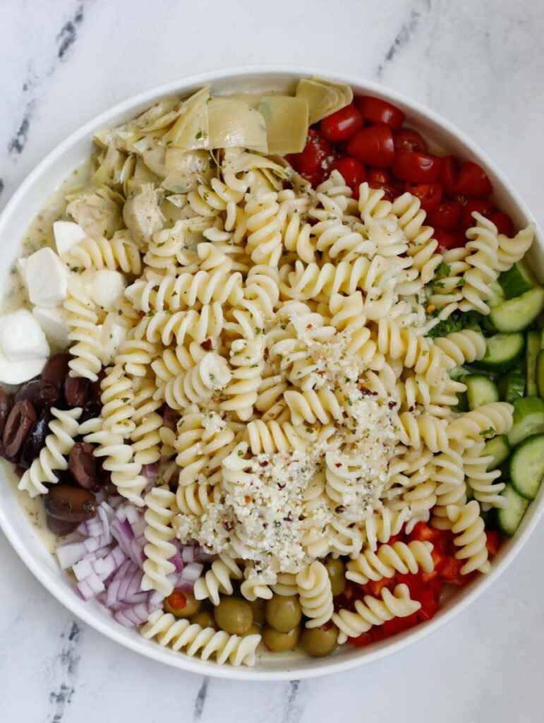 A bowl with ingredients for a pasta salad with dressing on top before mixing.