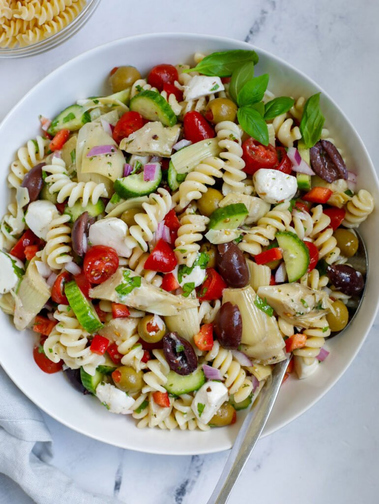 A bowl of Mediterranean pasta salad with a spoon on a marble service.