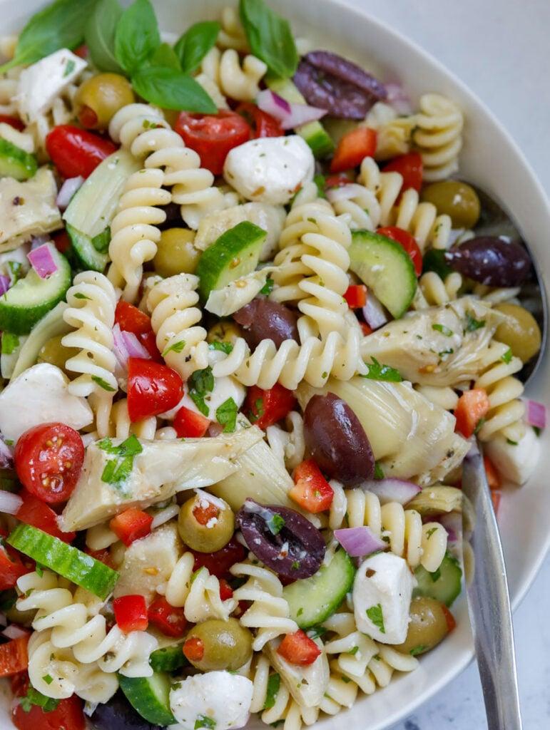Close up of a bowl of Mediterranean pasta salad.
