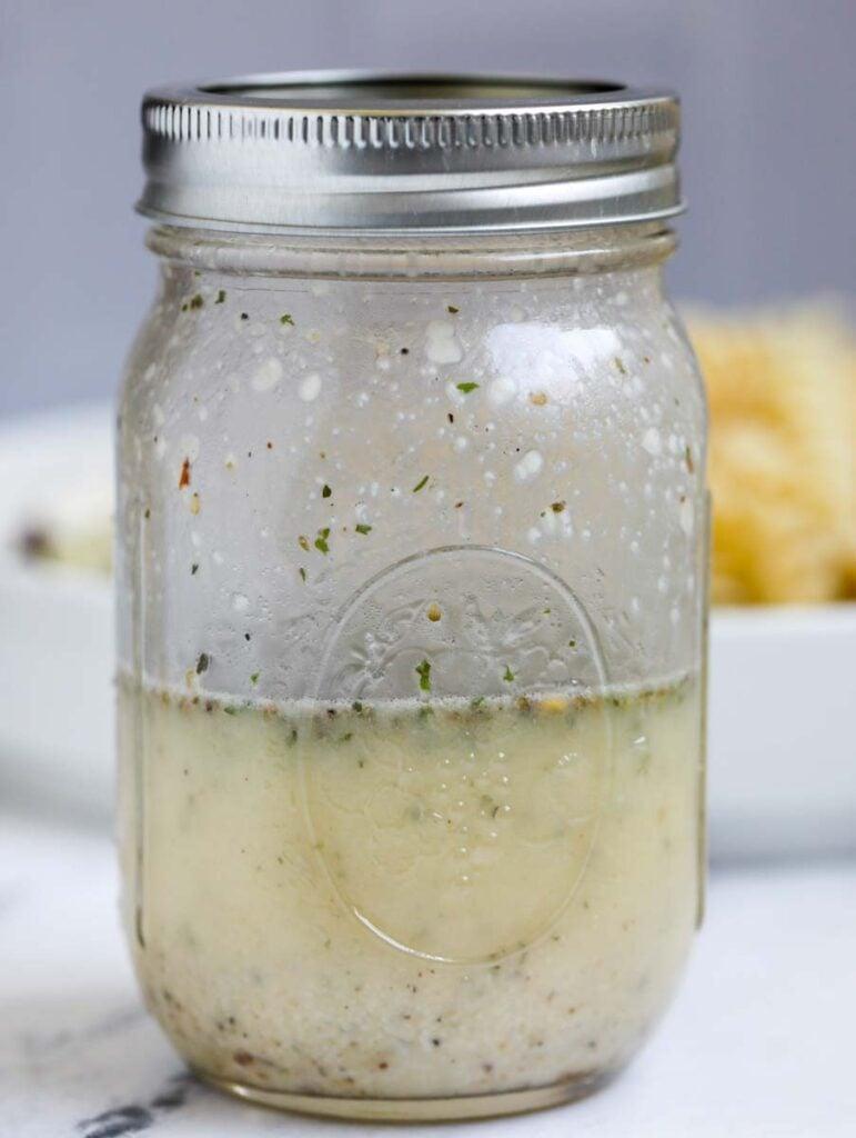 Mason jar with Greek dressing.