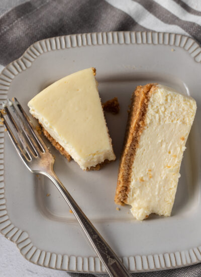 A slice of new york style cheesecake on a plate with the tip on the fork beside it.