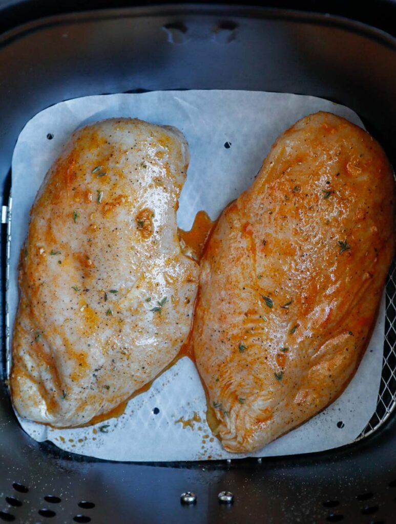 Two chicken breasts in an air fryer basket.
