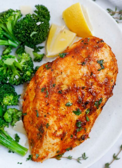 Close up of an air fryer rosemary chicken breast beside some broccoli and lemon wedges.
