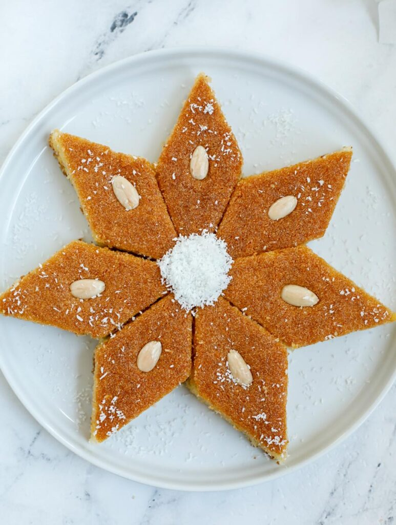 Seven pieces of Coconut Basbousa placed in a star shape.