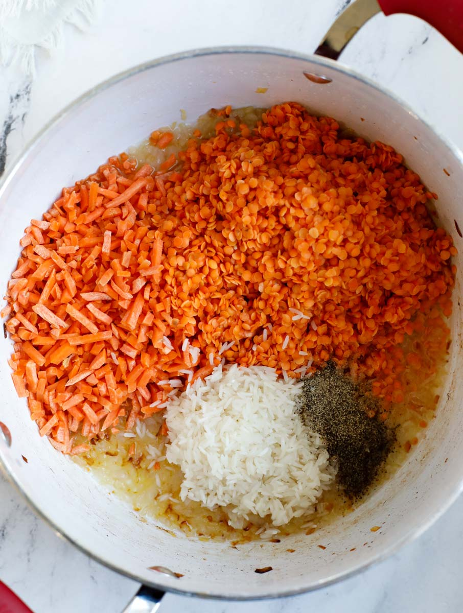 Pot with cooked onions and washed lentils, shredded carrots, rinsed riced, cumin powder and black pepper.