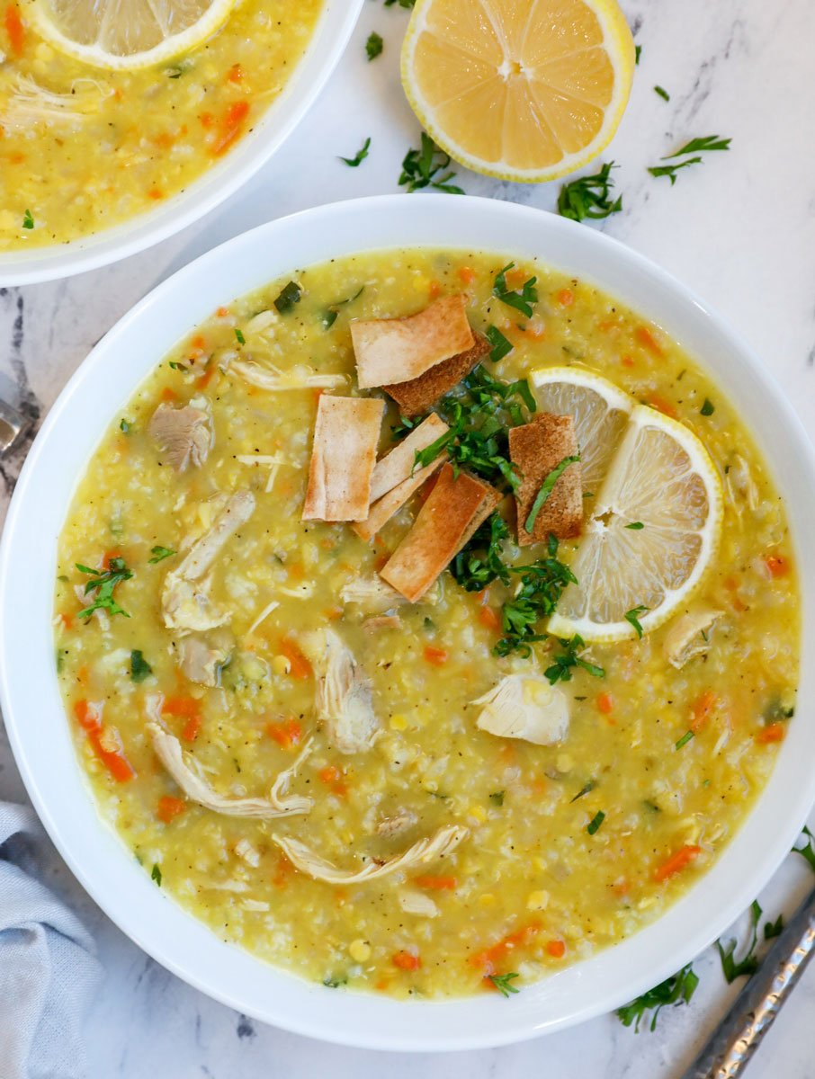 A bowl of chicken lentil and rice soup with sliced lemon and pita chips.