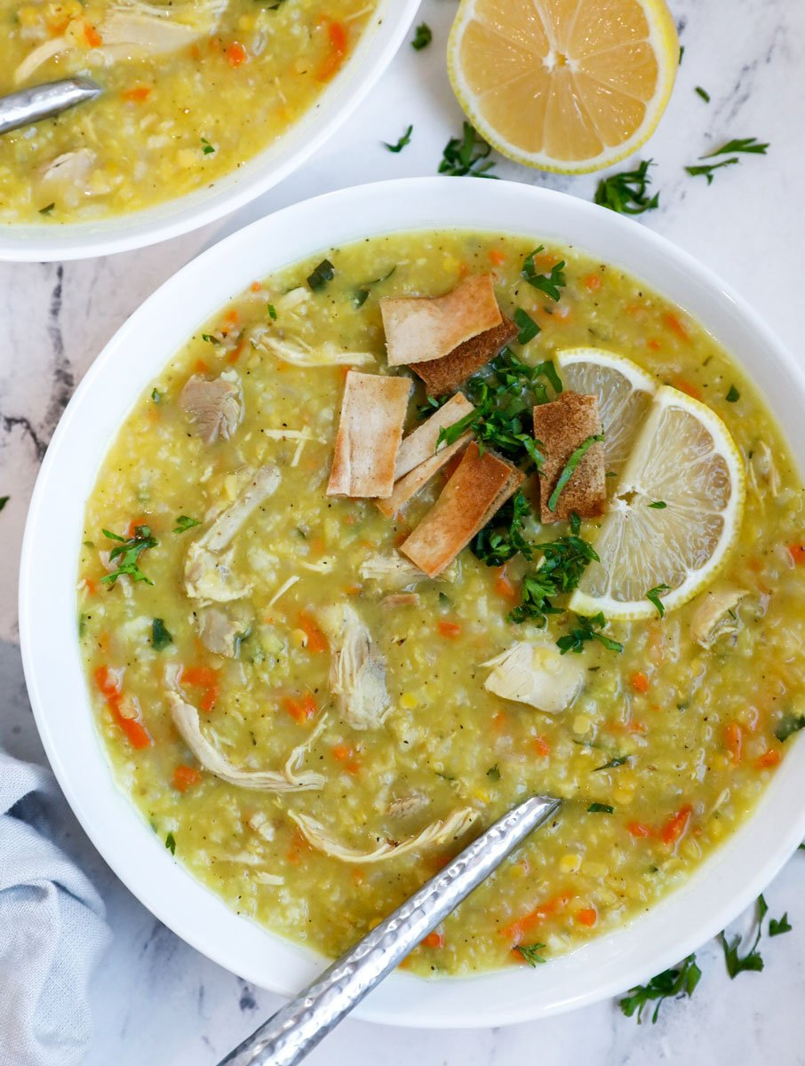 A bowl of chicken lentil soup with fried pita and lemon as garnish.