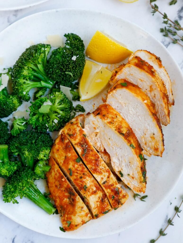 A plate of sliced air fryer rosemary chicken breast beside broccoli.