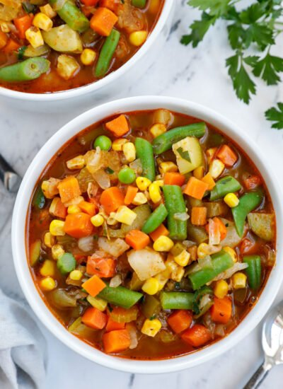 A white bowl of soup packed with veggies as a homemade vegetable soup.