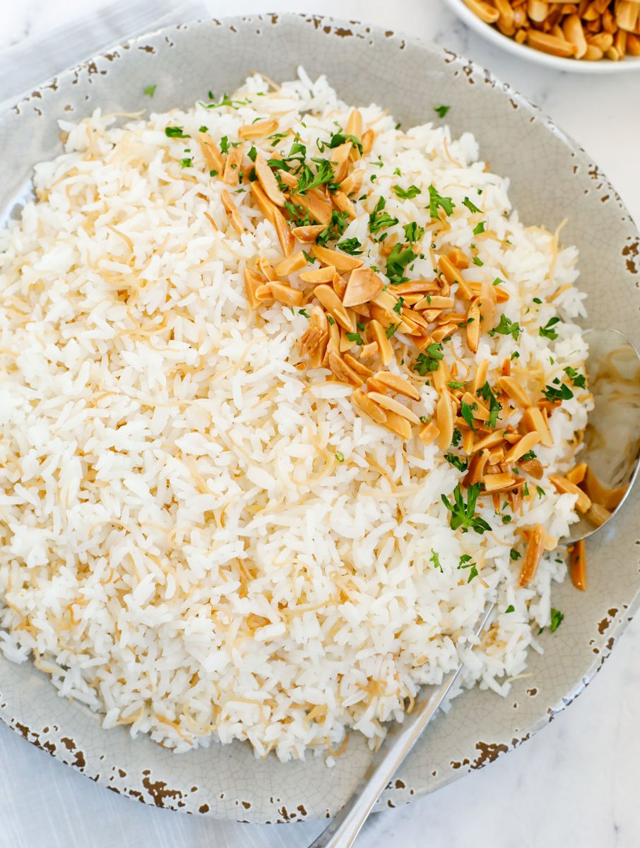 top down shot of vermicelli rice served on a plate with toasted almonds on top.