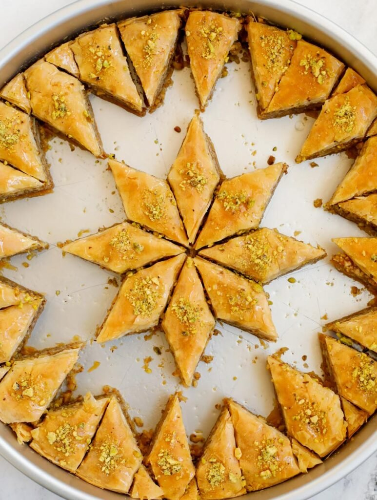 Walnut baklava in a pan with pieces removed.