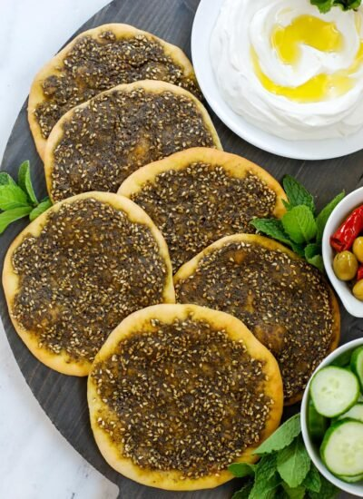 top down shot of zaatar manakeesh on a dark board with labneh, cucumber and olives