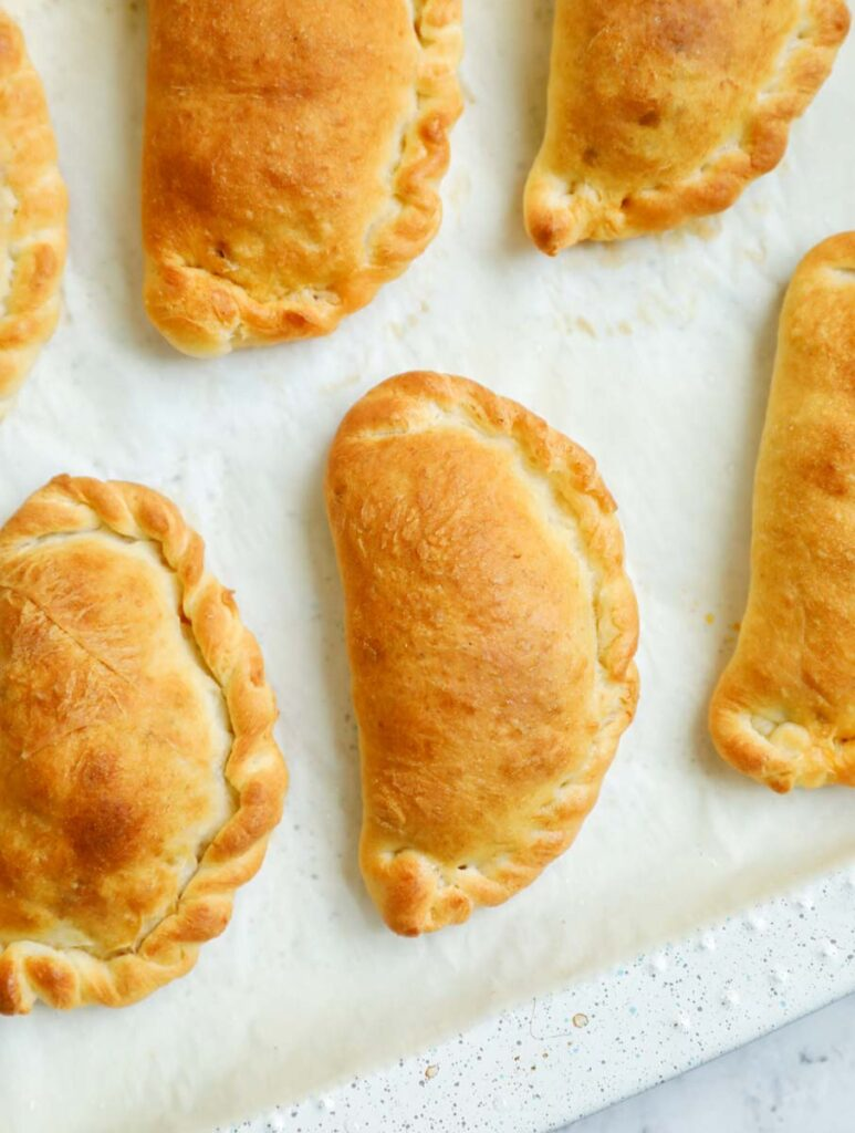 Baked meat pies on a parchment sheet.