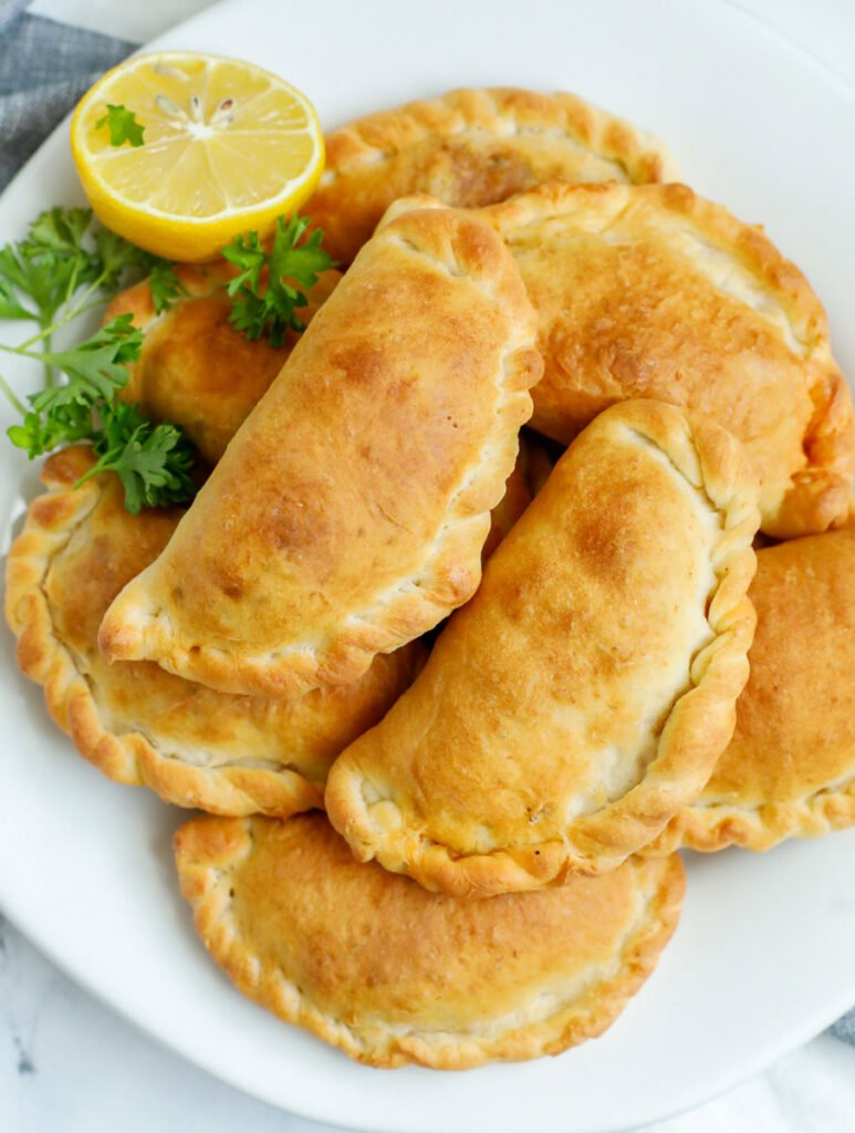 A platter of freshly baked individual meat pies.