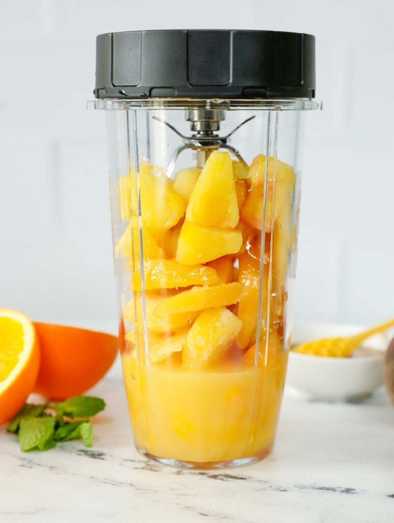Peach N' Orange slushie ingredients inside of a blender.