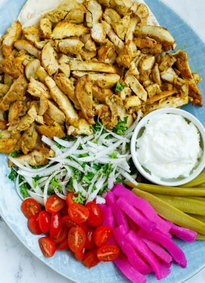 A platter of chicken shawarma with dip and sides.