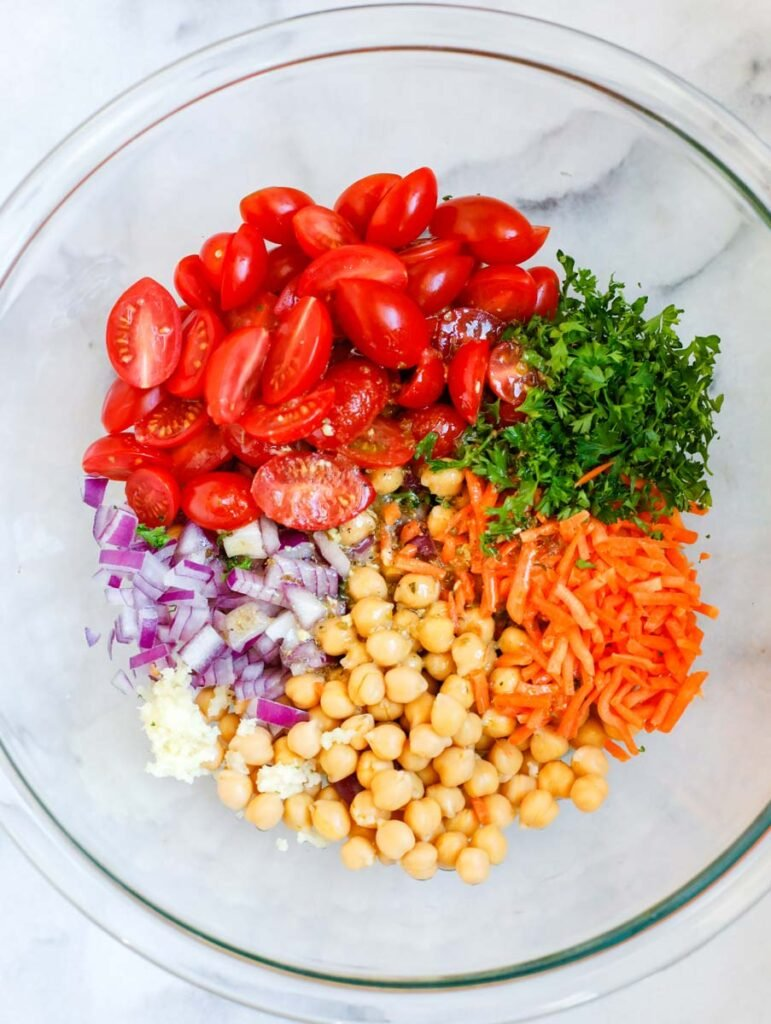 Large bowl with tomatoes, herbs, carrots, chickpeas, onions, and garlic.