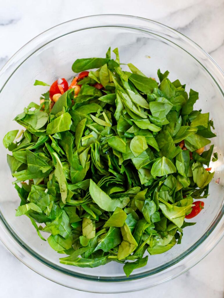 Spinach added to a bowl of salad.