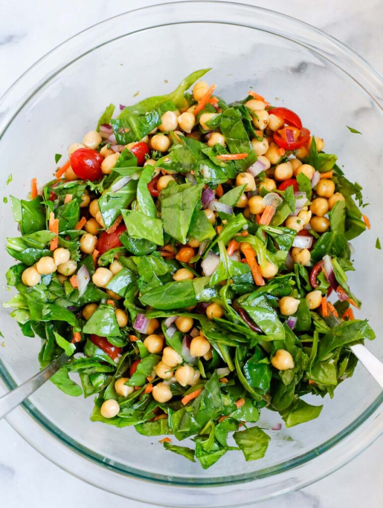 Spinach chickpea salad tossed together.
