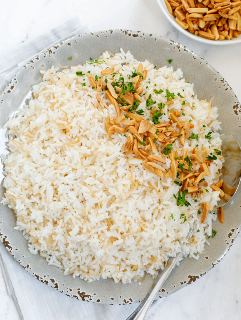 vermicelli rice served on a plate with toasted almonds and garnished with parsley