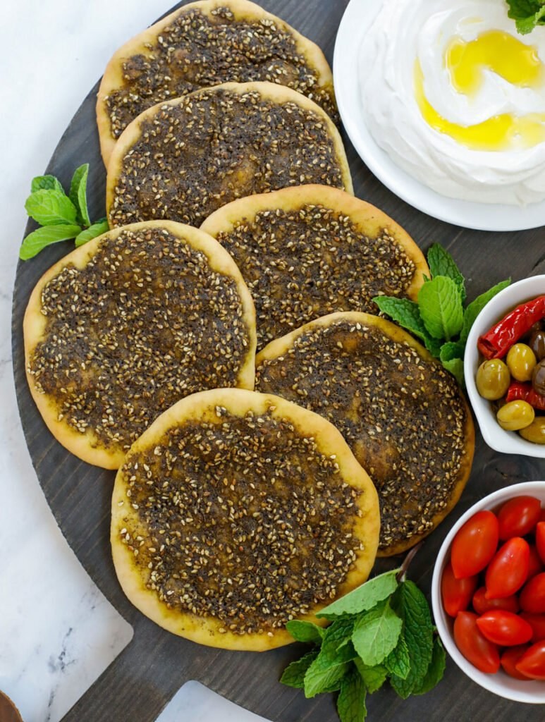 top down shot of the zaatar manakeesh on a dark board served with labneh