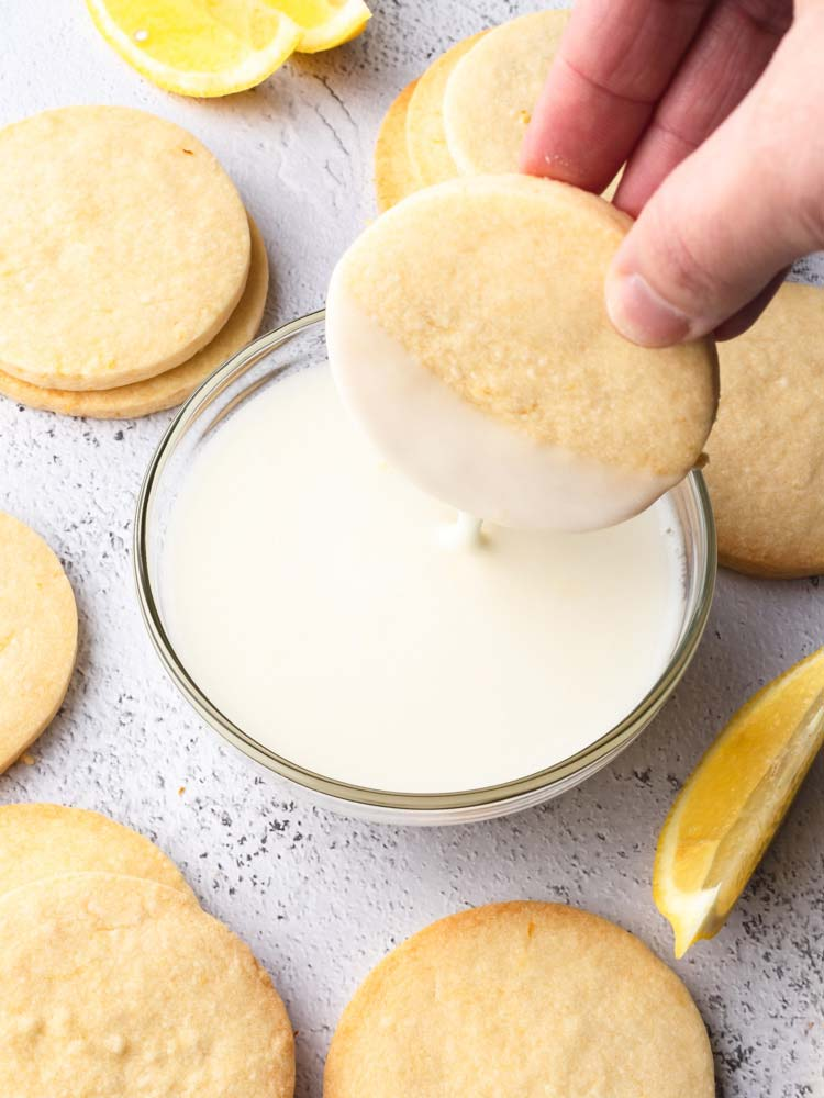 cookie being dipped half way into lemon icing