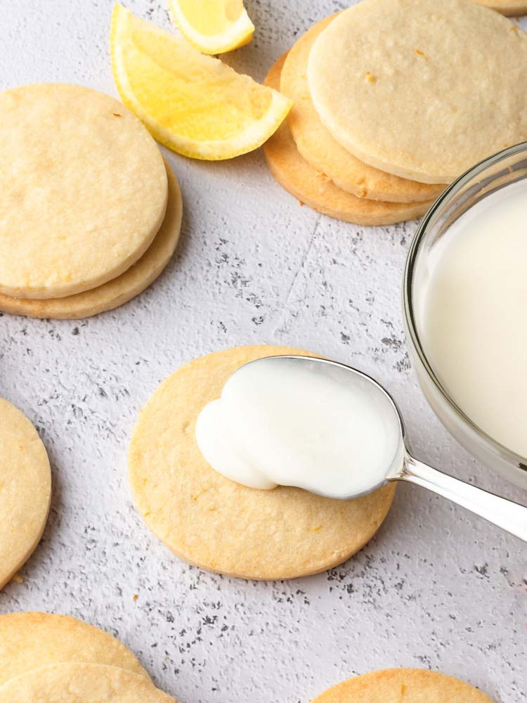 lemon icing being placed on a cookie