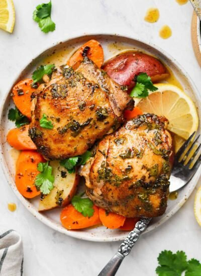 Two pieces of chicken thighs in a plate with veggies and fork