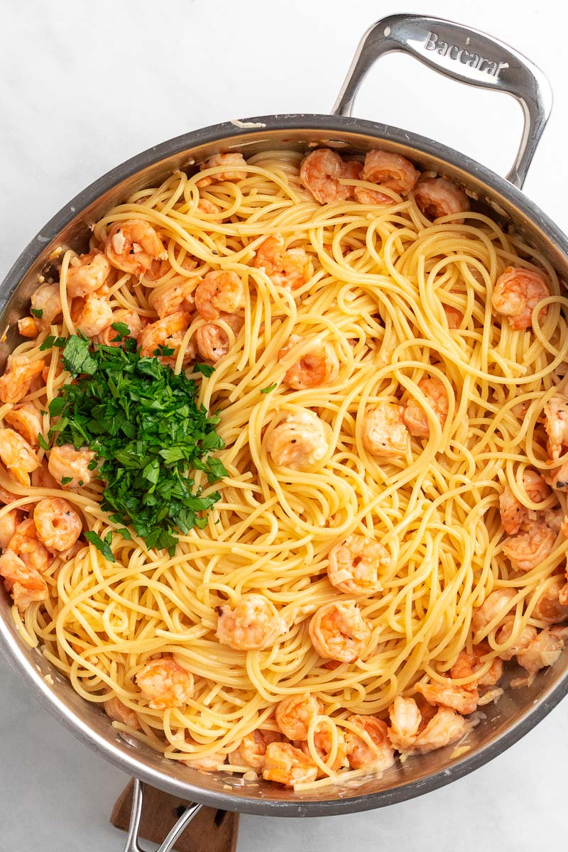 garlic shrimp spaghetti in a pan topped with parsley