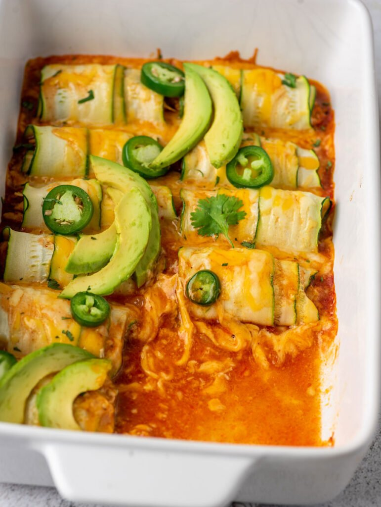 chicken enchiladas in a baking dish after baking with few pieces removed from the dish