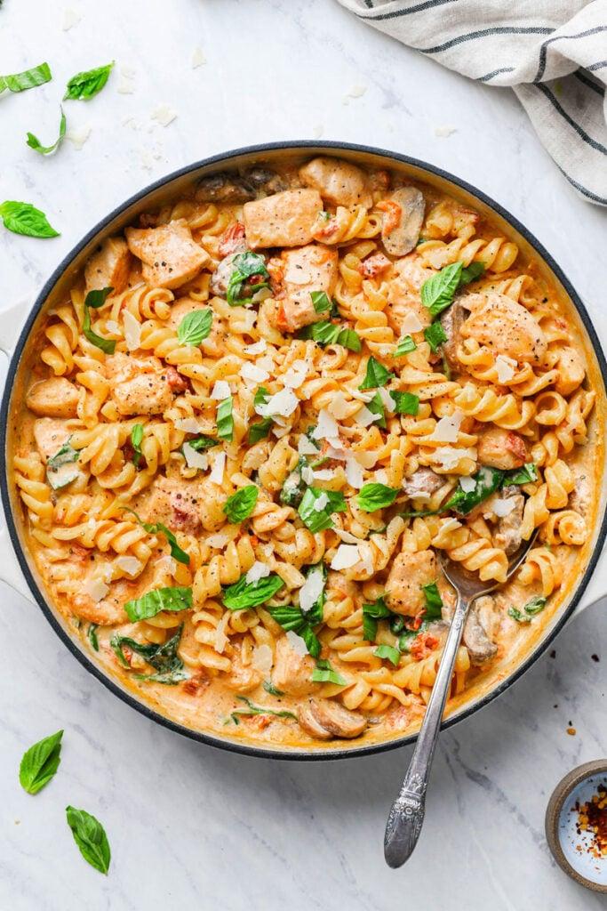 creamy mushroom chicken pasta in a skillet garnished with basil
