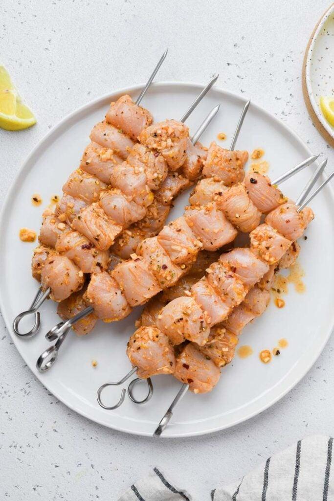 marinated greek chicken skewers before grilling