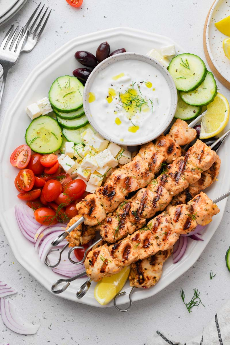 top down shot of the greek chicken skewer dish served with sides