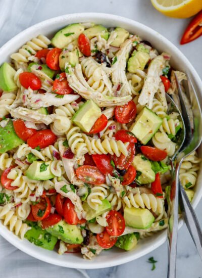 A bowl of avocado chicken pasta salad with a fork and spoon in the bowl.