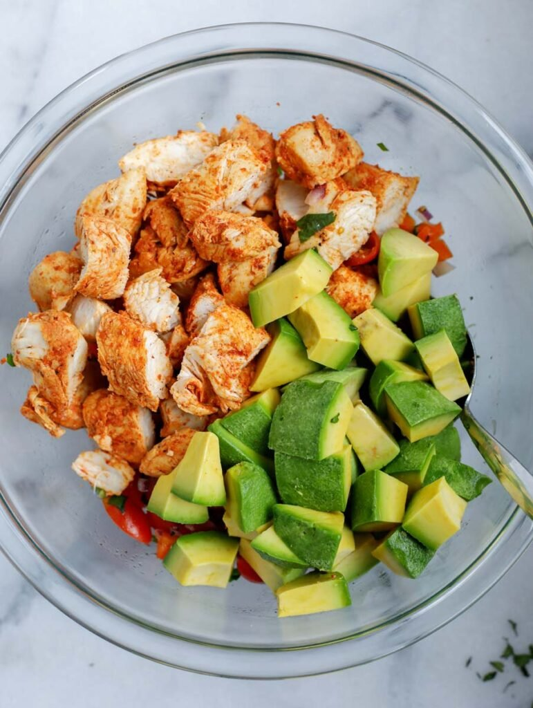 A bowl with the ingredients needed to make an avocado chicken salad.