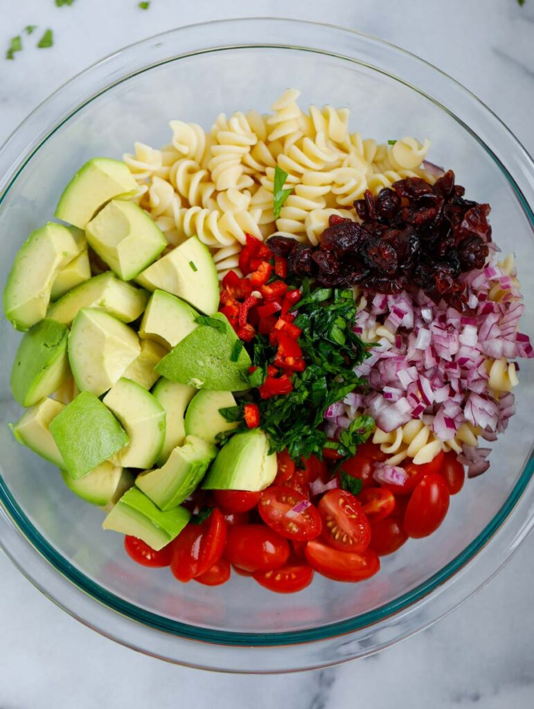 Ingredients for avocado chicken pasta salad chopped and in a bowl together.