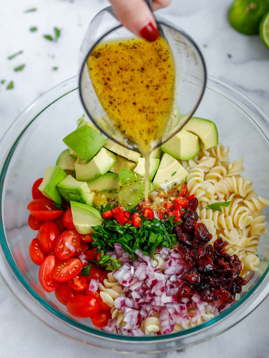 Dressing added to a bowl of avocado chicken pasta salad.