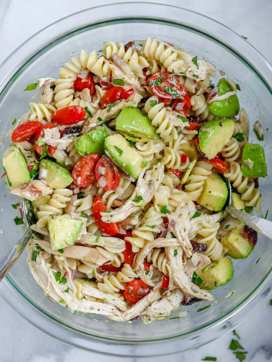 A bowl of avocado chicken pasta salad, mixed with salad dressing.