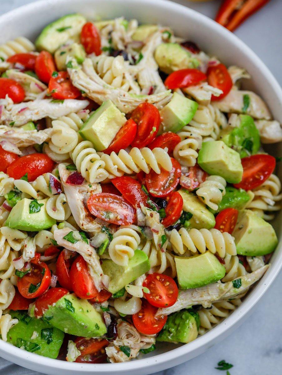 Close up of a bowl of avocado chicken pasta salad.