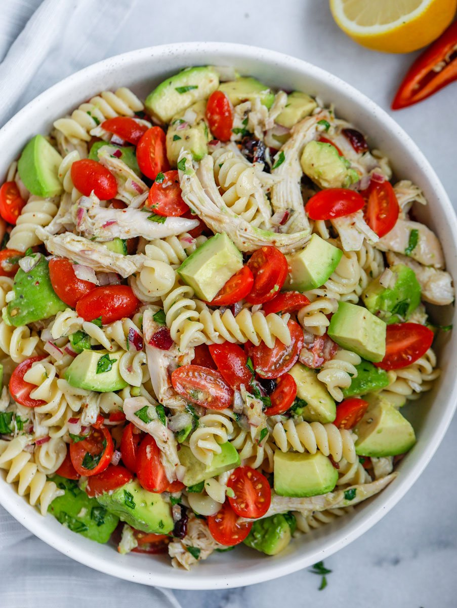 A bowl of avocado chicken pasta salad.