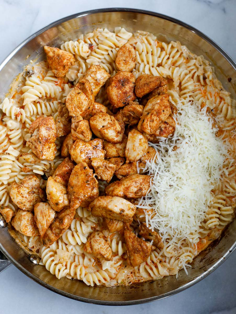Chicken and cheese added to the pan of cajun pasta.