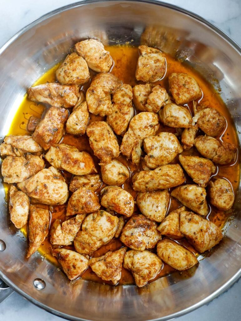 Cooked chicken cubes in a pan.