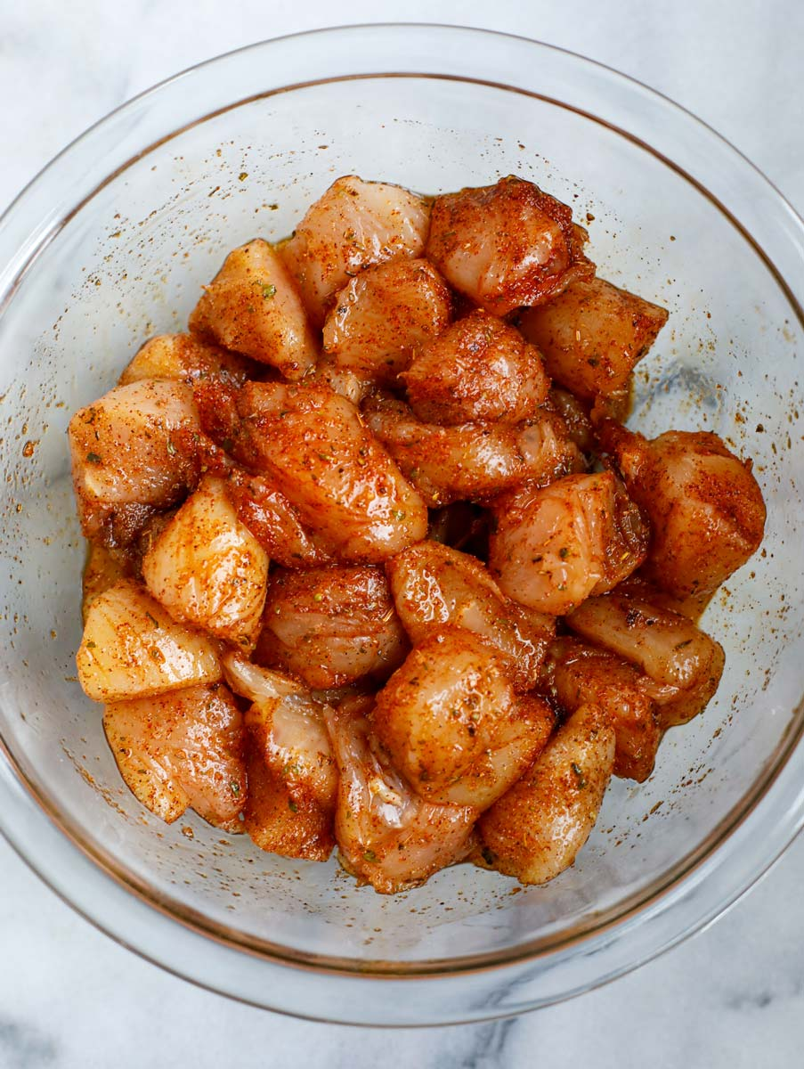 Seasoned marinating chicken cubes in a bowl.