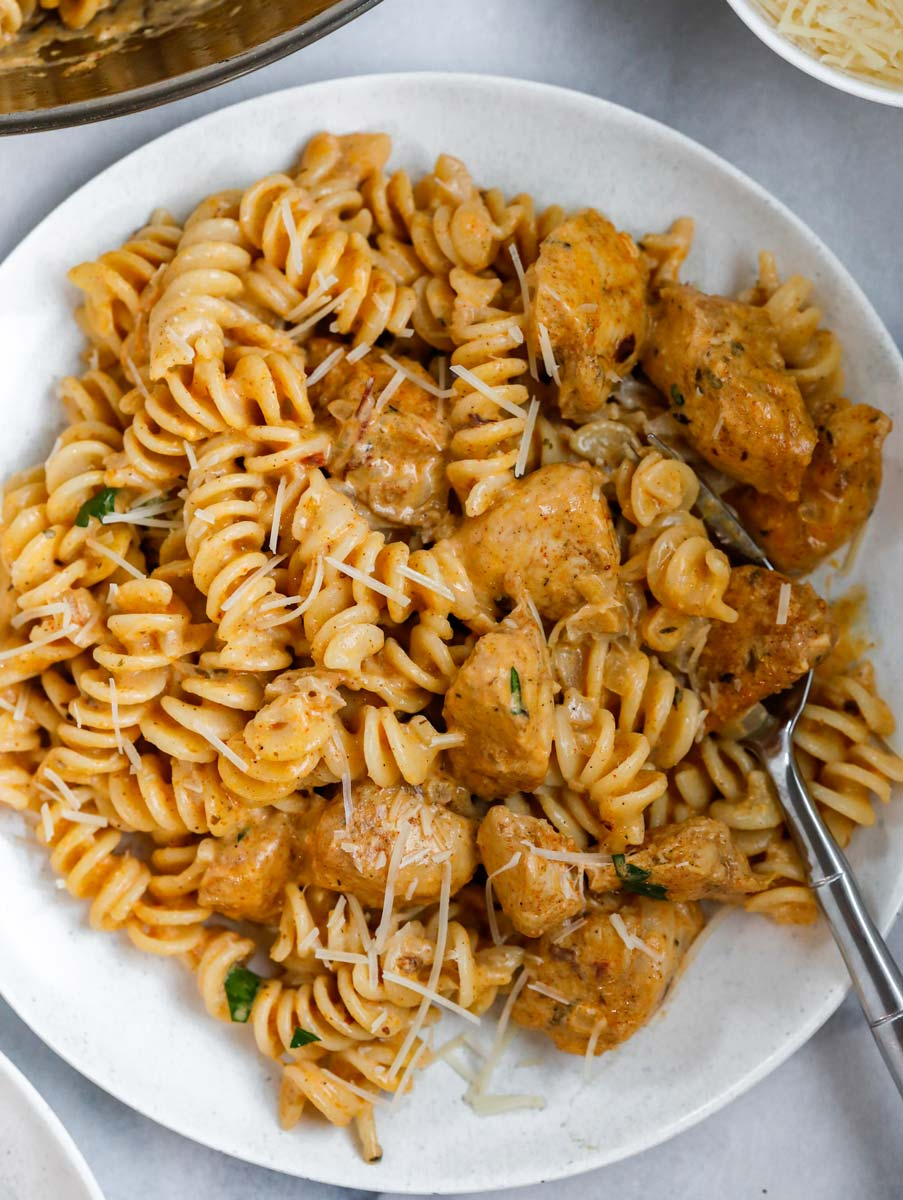 A bowl of creamy cajun chicken pasta with a fork inside.