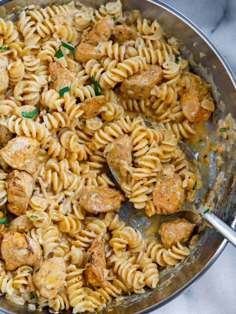 Close up of creamy cajun pasta with a spoonful of pasta and chicken.