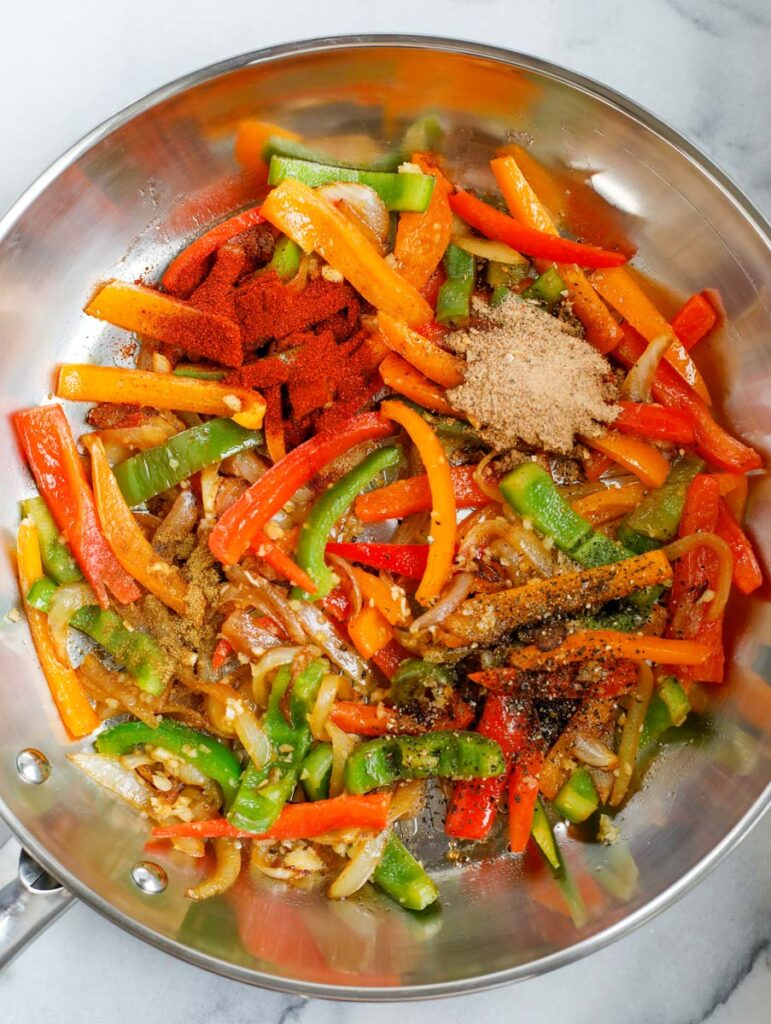 Seasoning added to a skillet of vegetables.