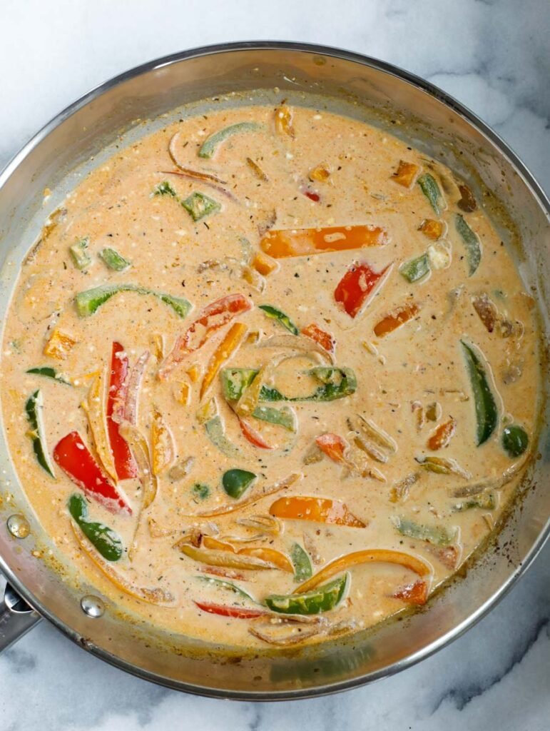Cream sauce being made in the skillet of vegetables.