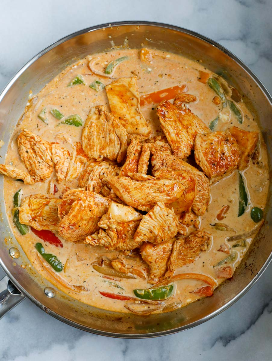 Chicken added to a pan of cream sauce and vegetables.
