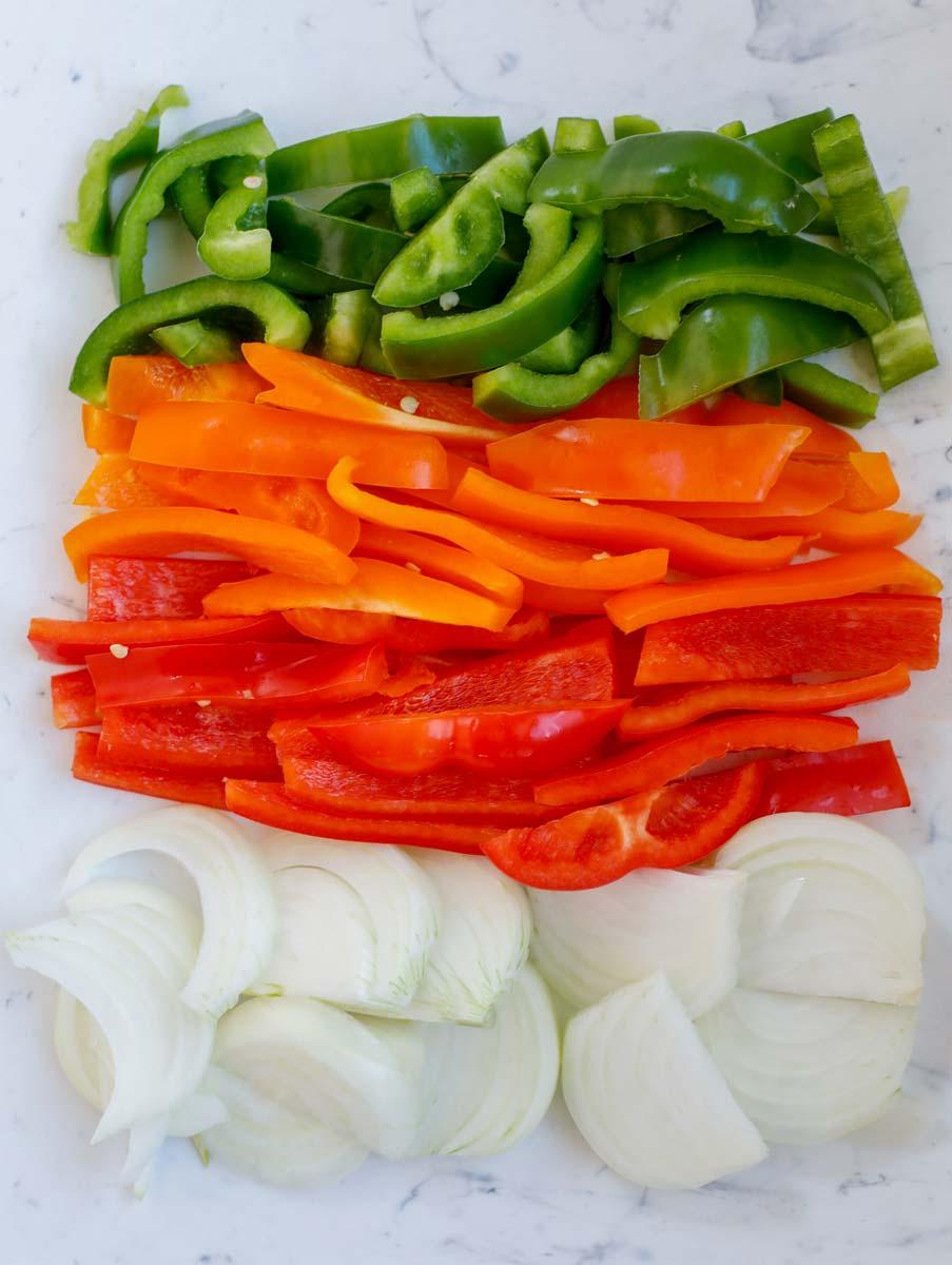 Green bell pepper, red bell pepper, orange bell pepper, and onions cut up.