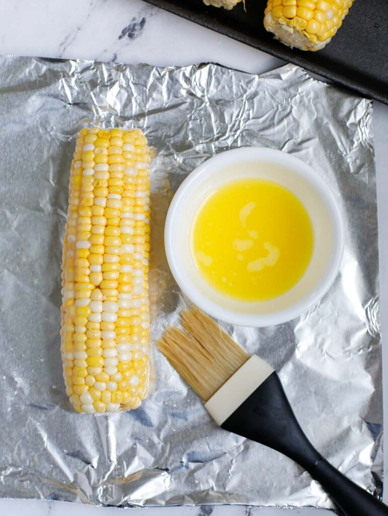 Butter brushed on a corn on the cob on top of tin foil.